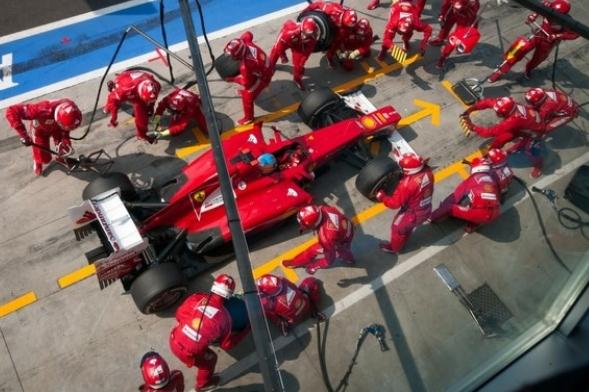Overview of Ferrari while technicians prepare the car on boxes